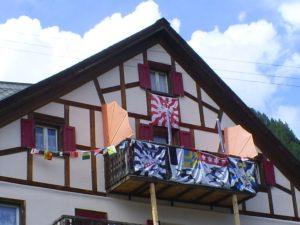 Geflammte und klassische Fahnen an einem Balkon