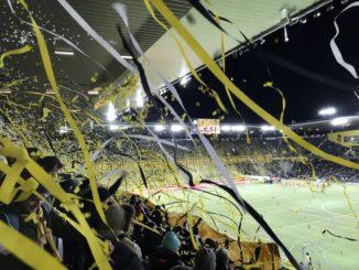 Fans mit Fahnen und Papierstreifen